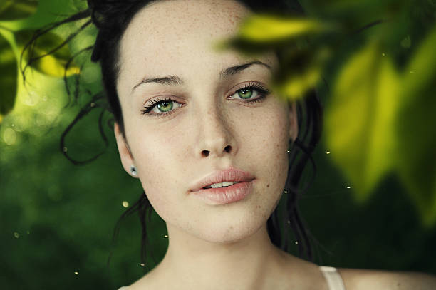 green sight a close-up portrait of young beautiful women in leaves dark spots face stock pictures, royalty-free photos & images