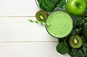Green smoothie above view with kale, avocado, spinach, apple and kiwi against a white wood background