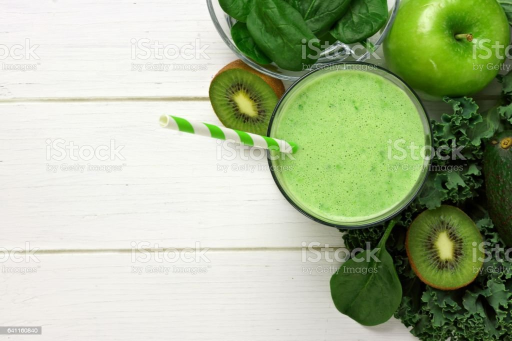Green smoothie above view with ingredients against white wood stock photo