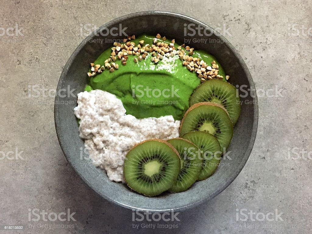 Green smoothie and coconut chia pudding bowl with buckwheat, kiwifruit stock photo