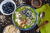 Green smoothie bowl with almonds, blueberries, chia and sunflower seeds, healthy superfood breakfast concept