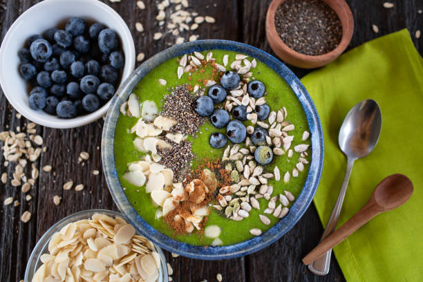 Green smoothie bowl with almonds, blueberries, chia and sunflower seeds stock photo