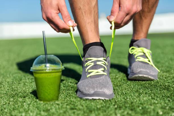 grüner smoothie fitness mann binden laufschuhe - mensch isst gras stock-fotos und bilder