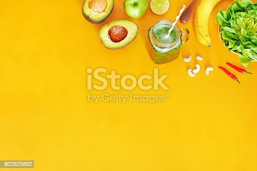 istock Green smoothie ingredients over yellow background with copy space. 822525502