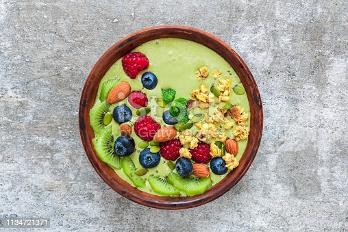 istock green smoothie matcha tea bowl with fruits, berries, granola, nuts and seeds. healthy vegan breakfast 1134721371
