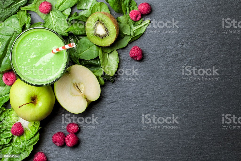 green smoothie with fruits and vegetables on black background stock photo