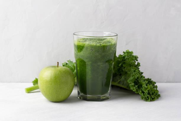 Grüner Smoothie mit Grünkohl und Apfel auf grauem Hintergrund – Foto