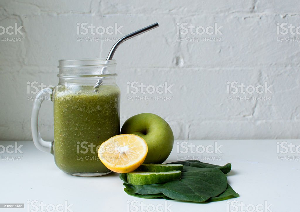 Green smoothie with metal straw stock photo