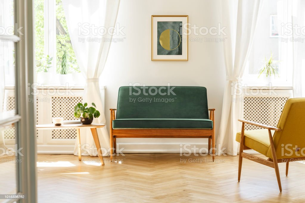 Picture of: Green Sofa With Dark Wooden Frame And A Comfy Yellow Armchair In A White Retro Living Room Interior With Natural Light Coming Through Big Windows Real Photo Stock Photo Download Image