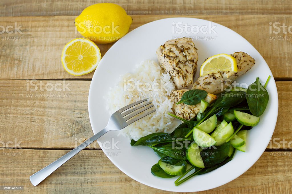 Green spinach and cucumber salad, white rice and chicken fillet stock photo