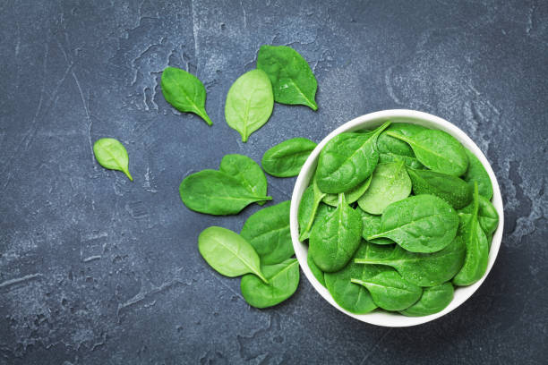 Green spinach leaves in bowl on black table top view. Organic and diet food. stock photo