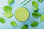 青いテーブル トップ ビューで緑のほうれん草のスムージー。朝食のためのデトックスとダイエット食品。