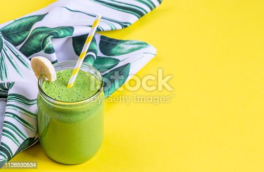 Green spinach smoothies in jar with chia seeds, healthy food concept, breakfast, yellow background