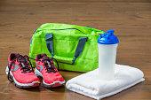 グリーン スポーツ フィットネスのボトルとタオルに近い袋とピンクのスニーカー