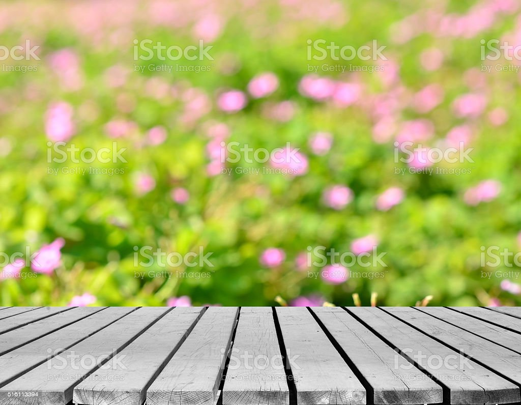 Green spring defocused abstract background and empty wooden platform stock photo