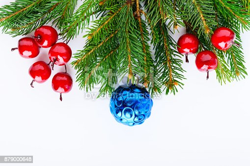 istock Green spruce branches decorated with balls, berries on a white background. New Year's, Christmas decor. Festive theme. Greeting card. 879000648
