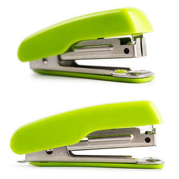 Green stapler isolated on white background Two staplers with a different orientation, is bright green color, and isolated on a white background. Studio shot in macro mode, with a nice natural shadow. stapler stock pictures, royalty-free photos & images