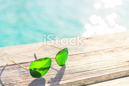 Green Sunglasses on a wooden deck, summer holiday concept