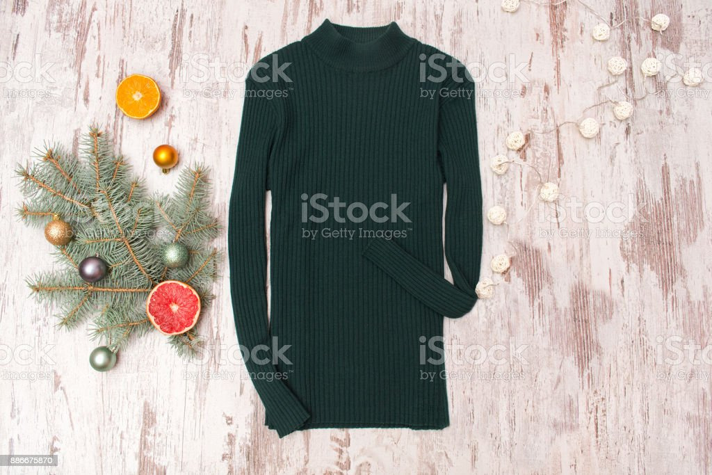 Green sweater, a decorated fir branch and a garland on a wooden background. Fashionable concept. stock photo