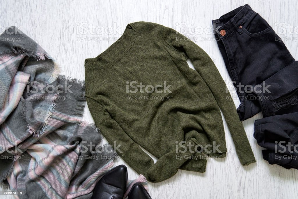 Green sweater, black jeans and a scarf. Fashionable concept stock photo