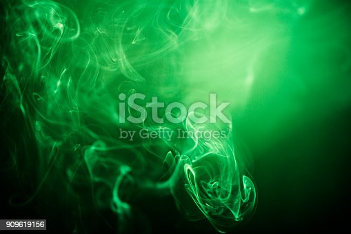 istock Green swirling smoke abstract close up on black background 909619156
