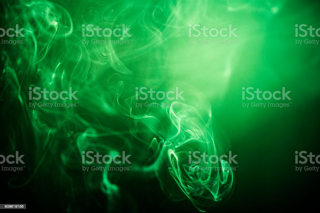 Green swirling smoke abstract close up on black background stock photo