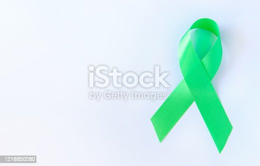 istock Green symbolic ribbon - the problem of organ donation, mental health. On a White background 1218850280