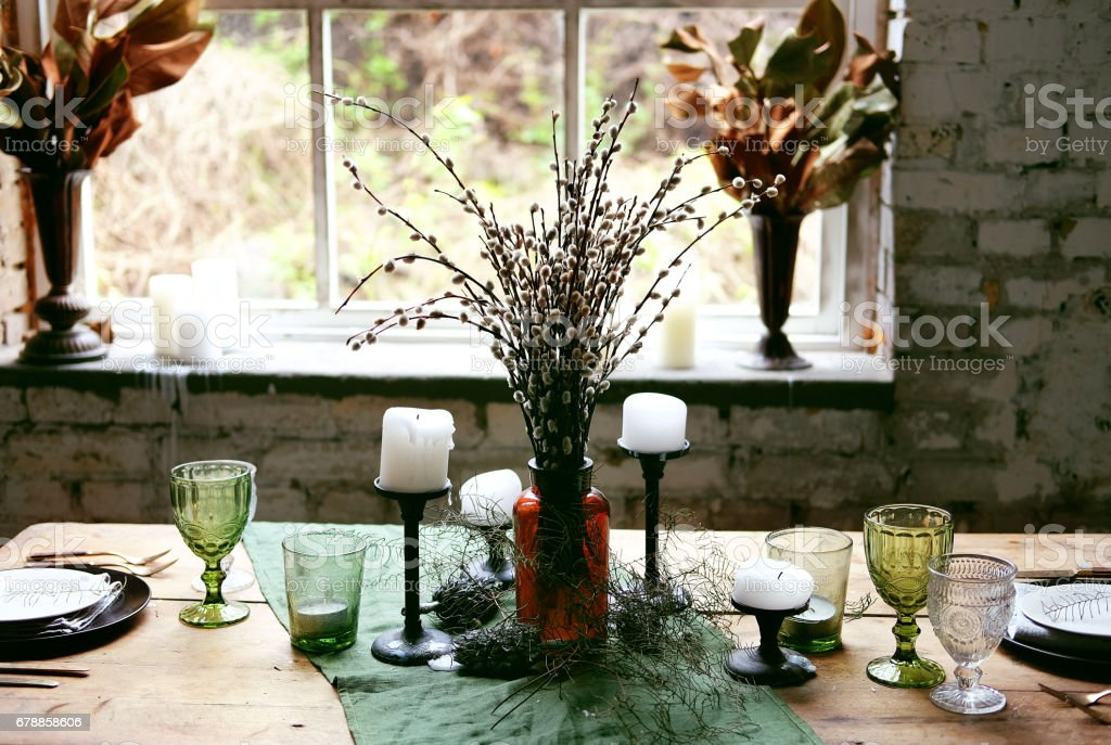 Green table setting for dinner with black and white plates, glass goblets, candles on wooden table. Rustic country objects. photo libre de droits