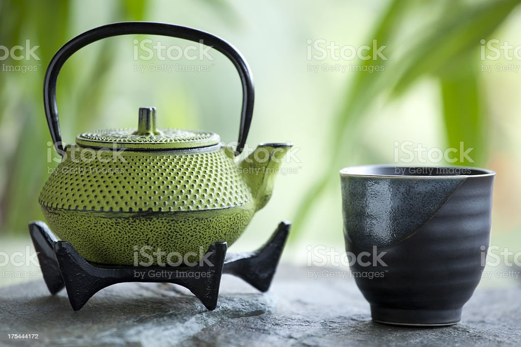 Green tea and cast iron teapot stock photo