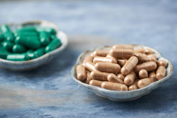 grüner tee und l-carnitine kapseln. konzept für eine gesunde nahrungsergänzung. rustikale holzhintergründe. platz kopieren. - grüner tee kapseln stock-fotos und bilder