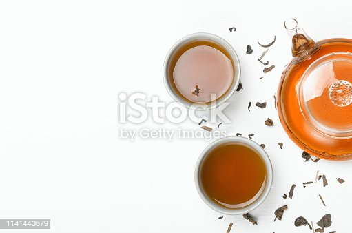 Green tea brewed in a transparent teapot and in small cups on a white table with scattered tea. Concept tea ceremony, Chinese traditions. Copy space, top view, flat lay