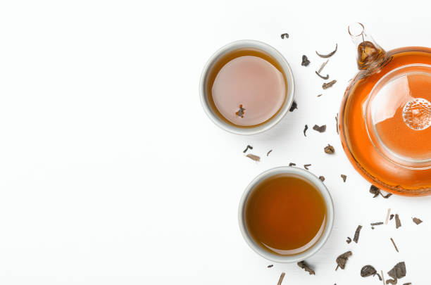 Green tea brewed in a transparent teapot and in small cups on a white table with scattered tea. Concept tea ceremony, Chinese traditions. Copy space, top view, flat lay. stock photo
