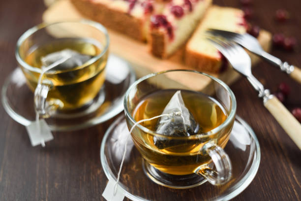 Green tea brewed in pyramid tea bags in glass cups and berry pie. Healthy beverage Green tea brewed in pyramid tea bags in glass cups and berry pie. Healthy beverage selective focus steep stock pictures, royalty-free photos & images