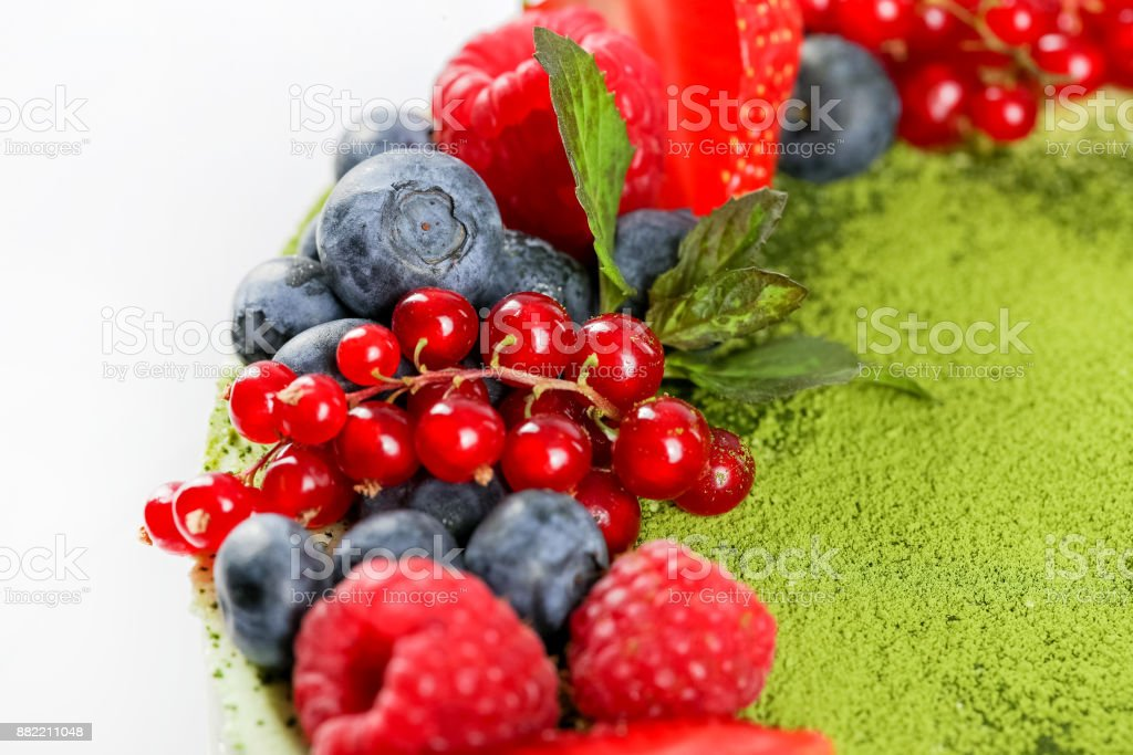 Green tea cake garnished with berries stock photo