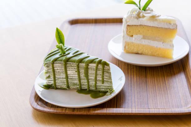 grüner teekuchen auf einem holzteller - grüntee kuchen stock-fotos und bilder