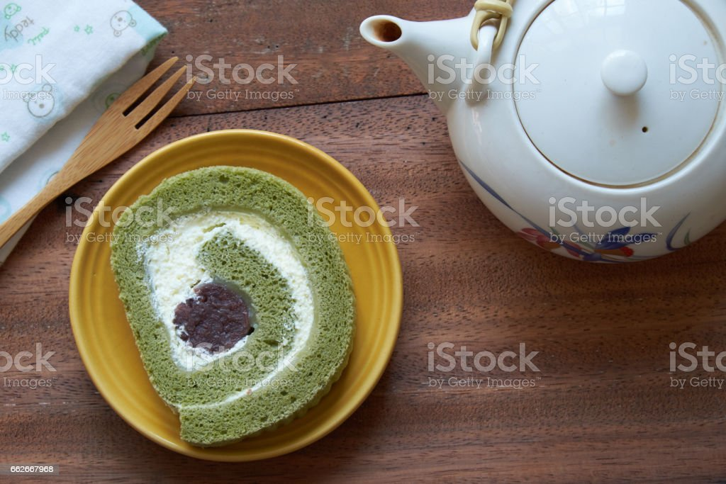 Green tea cake roll and tea pot on wooden background. – Foto