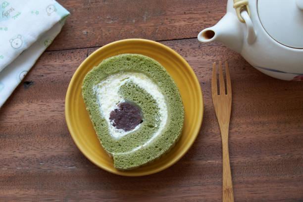 grüner tee kuchen rolle und teekanne auf holzhintergrund. - grüntee kuchen stock-fotos und bilder