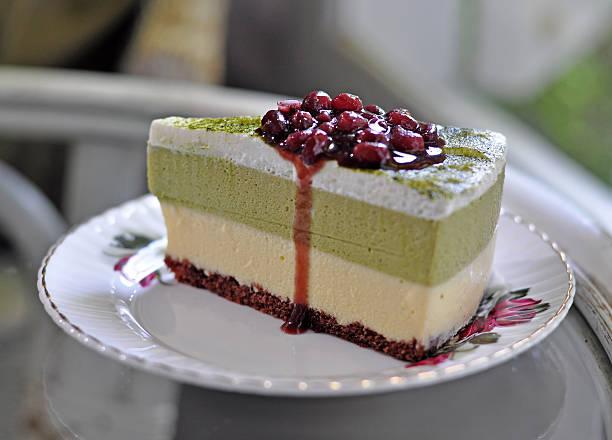 grüner tee und kuchen serviert mit einer sauce aus roten bohnen - grüntee kuchen stock-fotos und bilder