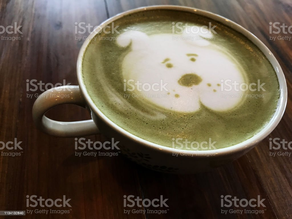 Green tea Cute dog face latte art in white cup on wooden table ;...