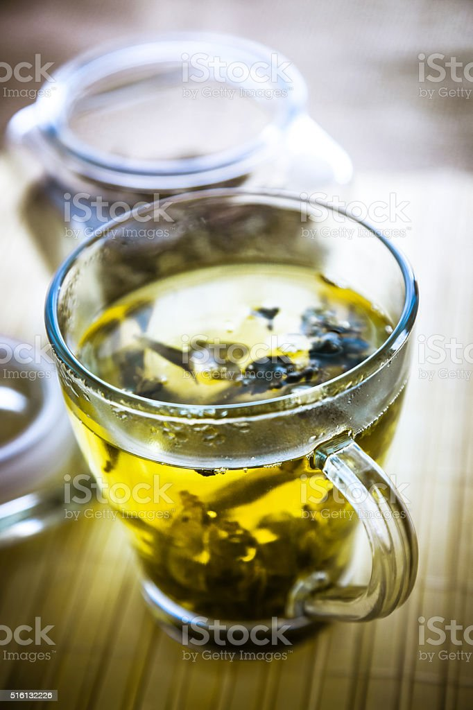 Green tea in a glass teacup on wooden table stock photo