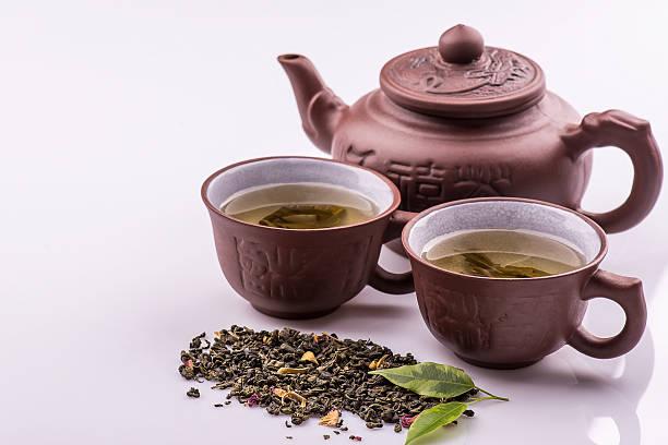 grüner tee in tasse, teekanne auf bambus matten, weißer hintergrund - jasmin party stock-fotos und bilder