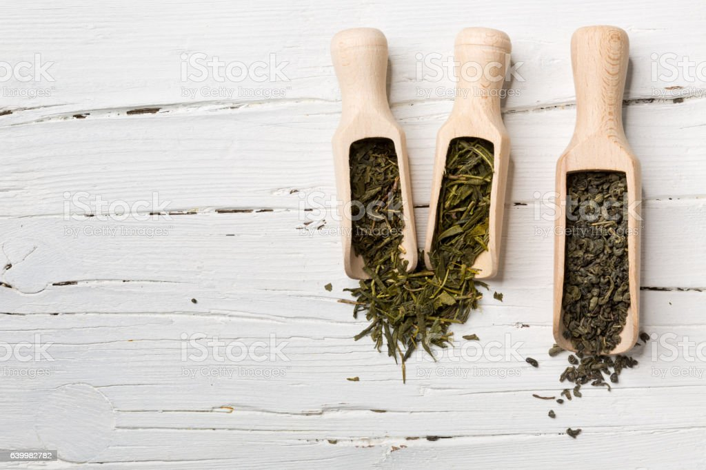 Green tea leaves in scoop on white wooden background. stock photo