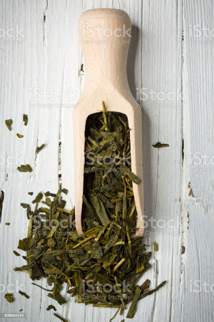 green tea leaves with scoop on wooden background stock photo