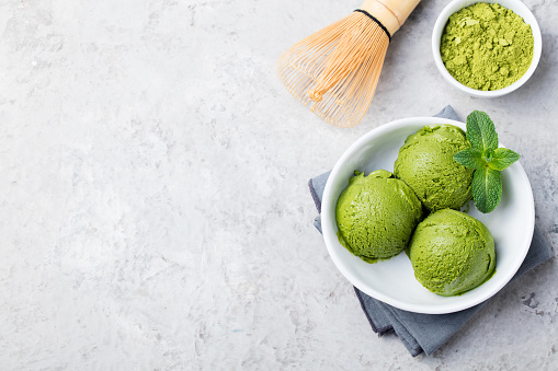 Green tea matcha ice cream scoop in white bowl on a grey stone background. Copy space. Top view