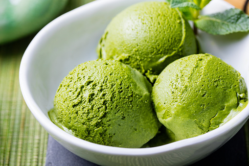 Green tea matcha ice cream scoop in white bowl on a wooden background. Close up.