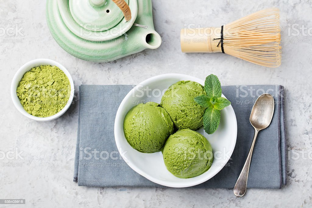 Green tea matcha ice cream scoop in white bowl stock photo