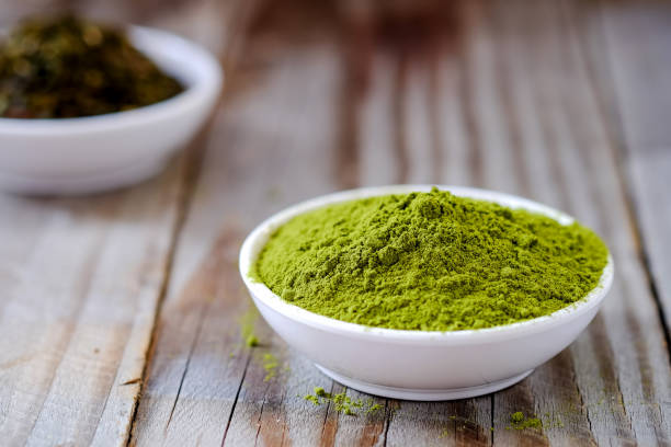 Green tea powder with dried tea in white cup. stock photo