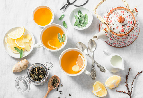 Green tea with lemon, ginger, sage on a light background, top view. Healthy detox drink. Tea ceremony