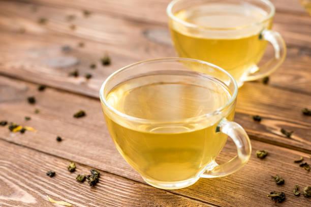 grüner tee mit minze, rose, goji-beeren und ananas in tassen - grüner tee koffein stock-fotos und bilder