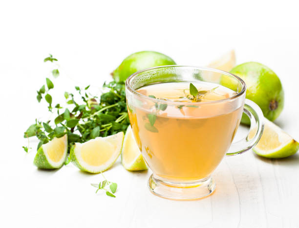 Green  tea with thyme and lime on white background stock photo
